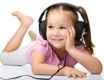 Cute little girl enjoying music using headphones Royalty Free Stock Photos