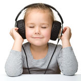 Cute little girl enjoying music using headphones Stock Photos