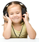Cute little girl enjoying music using headphones Royalty Free Stock Images