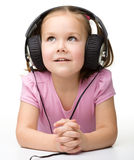 Cute little girl enjoying music using headphones Royalty Free Stock Images