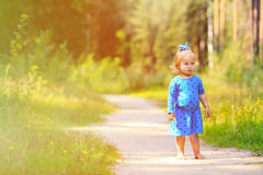 Cute little girl enjoying nature, playing in. Cute little girl walking in summer forest, kids summer outdoor activities Stock Photo
