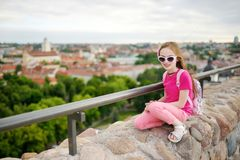 Cute little girl enjoying a view of Vilnius city from the Gediminas hill. Exploring tourist attractions with kids royalty free stock photos