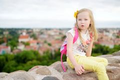 Cute little girl enjoying a view of Vilnius city from the Gediminas hill. Exploring tourist attractions with kids stock photo