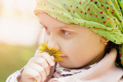 Cute little girl enjoys the smell of flowers on the yellow field Stock Photo