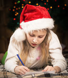 A cute little girl with enthusiasm writes a letter to Santa Stock Photography