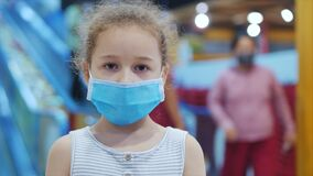 Cute little girl from an epidemic of coronaviruses or viruses looks at the camera among people in masks from the virus