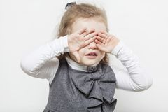 Cute little girl, evil emotion, close-up, light background royalty free stock photos