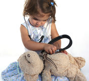 Cute little girl examining teddy. Cute little girl examining her teddy bear with a medical stethoscope Royalty Free Stock Image