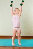 Little girl lifting up dumbbells Stock Photo
