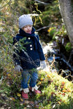 Cute Little Girl exploring autumn woods by spring stream. Stock Photography
