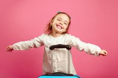 Cute little girl extended arms, depicts a plane, smiling happily, stands near suitcase on pink. royalty free stock photos