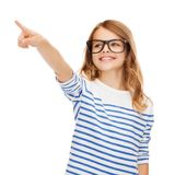 Cute little girl in eyeglasses pointing in the air. Education, school and imaginary screen concept - cute little girl in eyeglasses pointing in the air or Royalty Free Stock Image