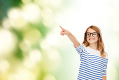 Cute little girl in eyeglasses pointing in the air Stock Photo