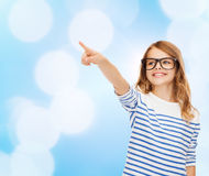 Cute little girl in eyeglasses pointing in the air Royalty Free Stock Images
