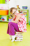 Cute little girl in eyeglasses sitting on stack of books Royalty Free Stock Image
