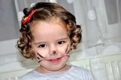 Cute little girl with face painted like cat Royalty Free Stock Image