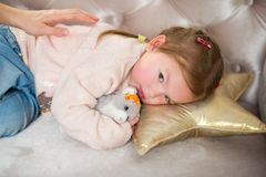 Cute little girl falls asleep on a pink sofa. Child embraces a favourite soft toy.The mother`s hand caresses the baby stock photo