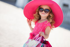 Cute little girl in fashion hat with shopping bags next to a supermarket Stock Photography