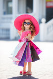Cute little girl in fashion hat with shopping bags next to a supermarket. Beautiful little girl with blond long curly hair, in a pink straw hat with large brim stock photos
