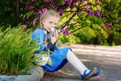 Cute little girl with a favorite toy donkey. Sitting on the background of a flowering bush Stock Photo
