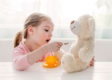 Cute little girl feeding toy teddy bear Royalty Free Stock Photo