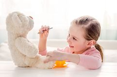 Cute little girl feeding toy teddy bear Royalty Free Stock Images