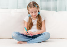 Cute little girl filling in a friends album Royalty Free Stock Photos