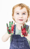Cute little girl with finger paint looking up Royalty Free Stock Photo