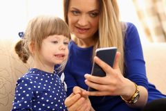 Cute little girl on floor carpet with mom. Use cellphone calling dad portrait. Life style apps social web network wireless ip telephony concept stock photo