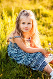 Cute little girl with flower. In evening sunlight Stock Image