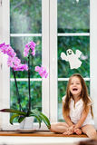Cute little girl with flower sitting on windowsill of new pvc wi Stock Images