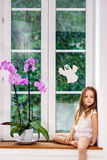 Cute little girl with flower sitting on windowsill of new pvc wi Royalty Free Stock Photography