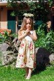 Cute little girl with flowers chaplet. In summer garden Stock Image