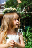 Cute little girl with flowers chaplet. In summer garden Royalty Free Stock Images