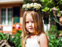 Cute little girl with flowers chaplet. In summer garden Stock Photography