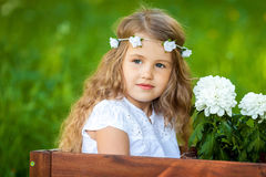Cute little girl with flowers. Cute little girl hiding in wooden box with flowers Royalty Free Stock Photos