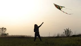 Cute little girl flying a kite in meadow at sunset stock footage