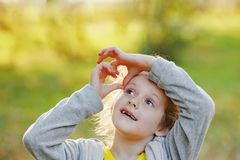 Cute little girl folded her hands in a heart shape in autumn pa. Rk Royalty Free Stock Photography