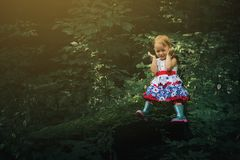 Cute little girl in the forest alone. Fairy tale beautiful light Royalty Free Stock Photography