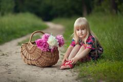 Cute little girl on a forest road with a basket of flowers. The concept of carefree childhood stock photography