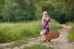 Cute little girl on a forest road with a basket of flowers. royalty free stock image