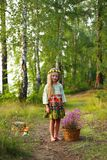 Cute little girl on a forest road with a basket of flowers. The concept of carefree childhood royalty free stock photography