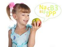 A cute little girl with a fresh apple Stock Photos
