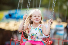 Cute little girl at fun fair, chain swing ride Royalty Free Stock Image