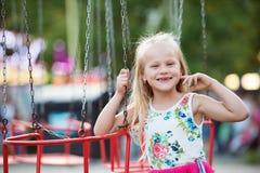 Cute little girl at fun fair, chain swing ride Stock Images