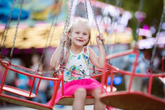 Cute little girl at fun fair, chain swing ride Royalty Free Stock Photo