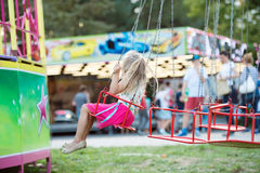 Cute little girl at fun fair, chain swing ride Royalty Free Stock Photography