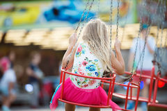 Cute little girl at fun fair, chain swing ride Royalty Free Stock Images