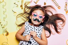 Cute little girl in funny glasses with paper mustache. stock image