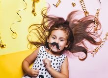 Cute little girl in funny glasses with paper mustaches on stick. Bright and festive background. Celebration masquerade portrait stock photos